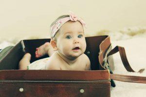 bébé fille allongée dans une valise vintage