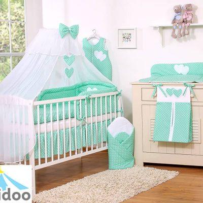 lit bébé avec linge de lit vert