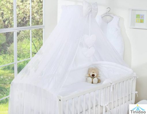 parure de lit blanc avec ciel de lit coeur